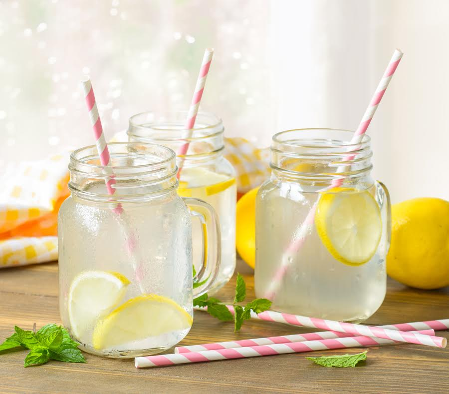 Homemade lemon drinks with straws against the window